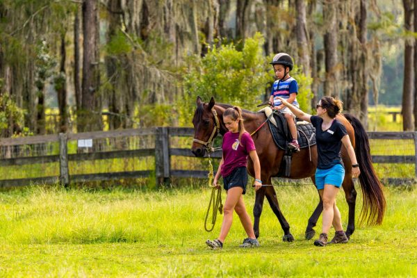 Volunteer leading Tie for a Therapeutic Riding lesson.